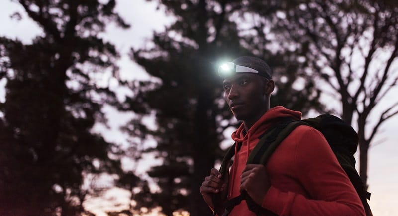 man wearing a headlamp at dusk