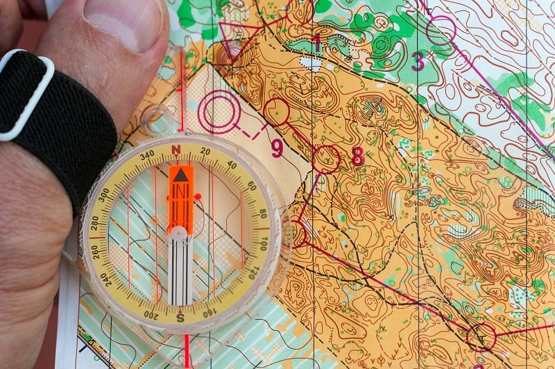 Hand holding a compass on an orienteering map