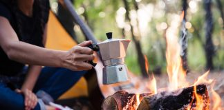 Couple making coffee on the bonfire with a percolator