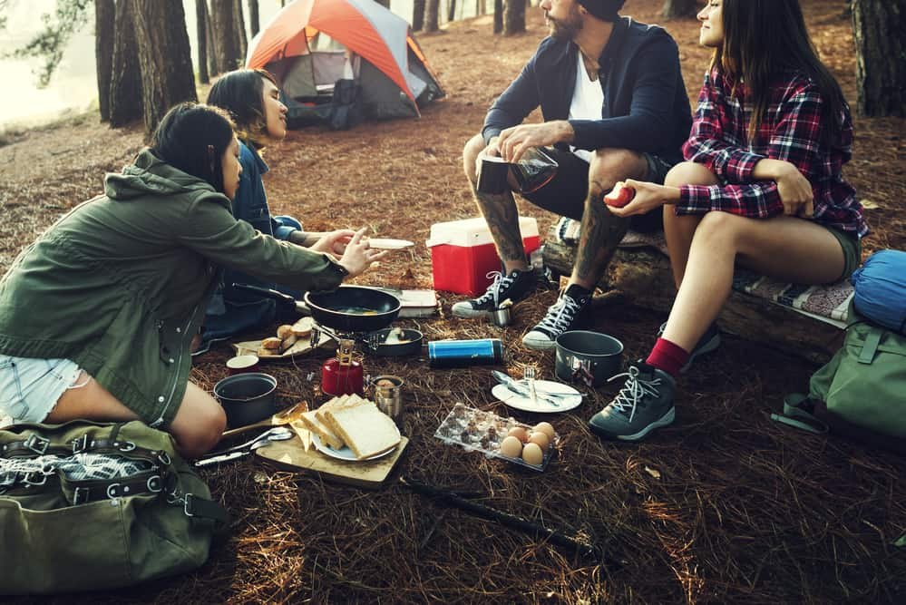 camping friends eating