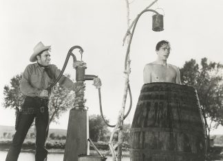 cowboy taking a shower outdoors in a barrel