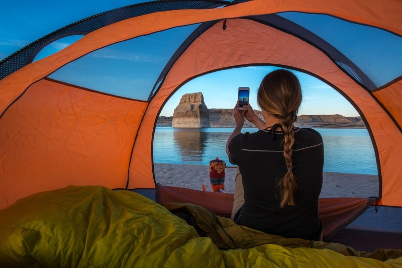 girl camping using a phone in her tent
