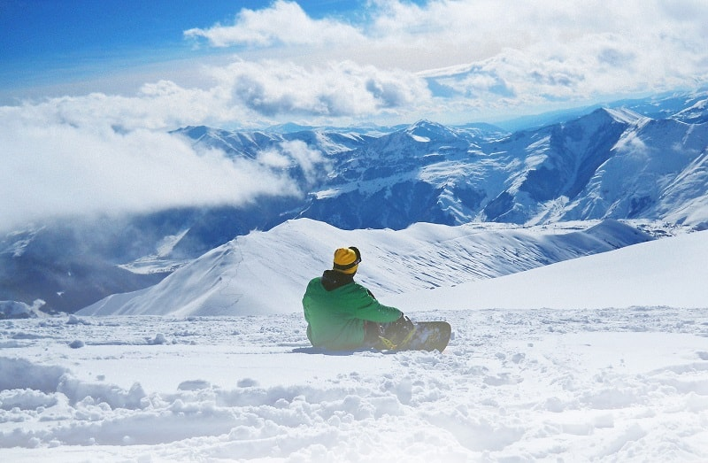 man on a snowboard sitting alone on the mountain